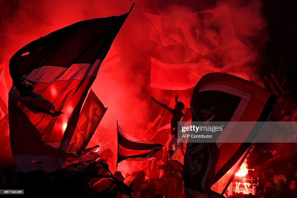 Paris Saint-Germain's supporters cheer with flags and flares during the French L1 football match between Paris Saint-Germain (PSG) and Nice (OGC Nice) on October 27, 2017, at the Parc des Princes stadium in Paris. /