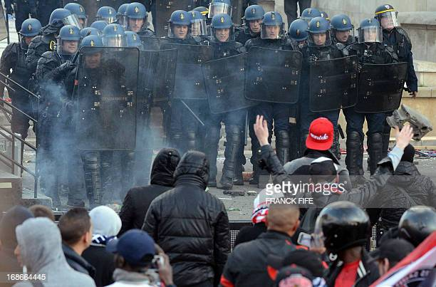 Paris SaintGermain's supporters face riot policemen during clashes on May 13 2013 in Paris one day after Paris secured French L1 football...