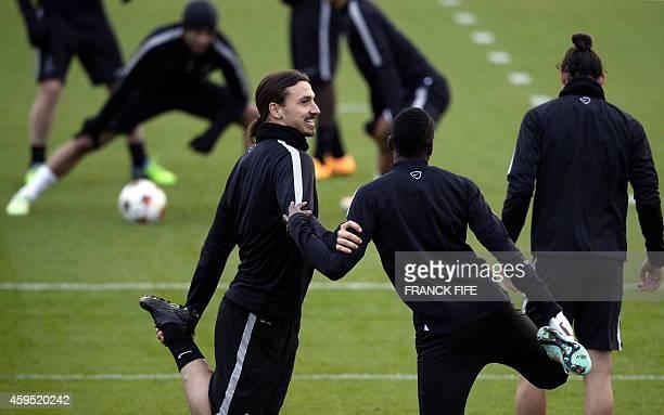 Paris SaintGermain's Swedish forward Zlatan Ibrahimovic and Paris SaintGermain's French midfielder Blaise Matuidi stretch during a training session...