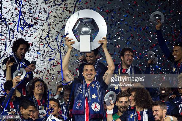 Paris Saint-Germain's Swedish forward Zlatan Ibrahimovic holds the trophy on the podium after winning the French L1 title at the end of the French L1...