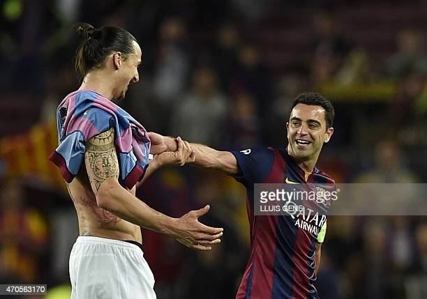 Paris Saint-Germain's Swedish forward Zlatan Ibrahimovic jokes with Barcelona's midfielder Xavi Hernandez at the end of the UEFA Champions League...