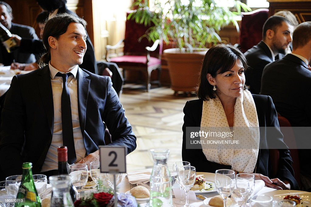Paris Saint-Germain's Swedish forward Zlatan Ibrahimovic (L) sits next to Paris' deputy mayor Anne Hidalgo during the annual lunch of the Paris-Saint-Germain's French L1 football club (PSG) team at the Paris city hall, on January 30, 2013.