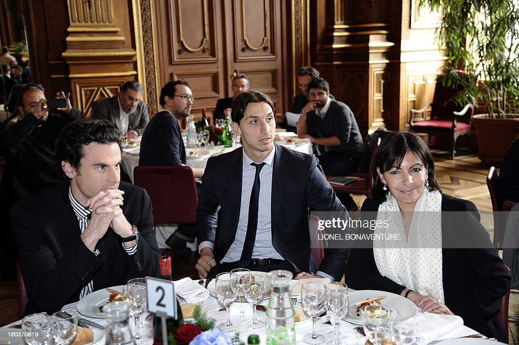 Paris Saint-Germain's Swedish forward Zlatan Ibrahimovic (C) sits next to Paris' deputy mayor Anne Hidalgo (R) during the annual lunch of the Paris-Saint-Germain's French L1 football club (PSG) team at the Paris city hall, on January 30, 2013.