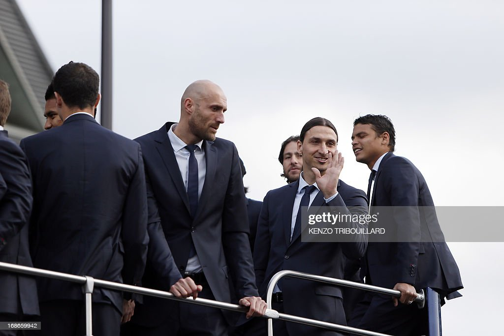 Paris Saint-Germain's Swedish forward Zlatan Ibrahimovic (2ndR) waves at supporters as he parade with teammates in a double decker on May 13, 2013 in Paris, one day after Paris secured French L1 football championship title.
