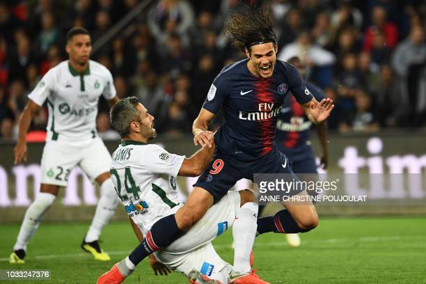 Paris Saint-Germain's Uruguayan forward Edinson Cavani falls after a tackle by Saint-Etienne's French defender Loic Perrin during the French L1...