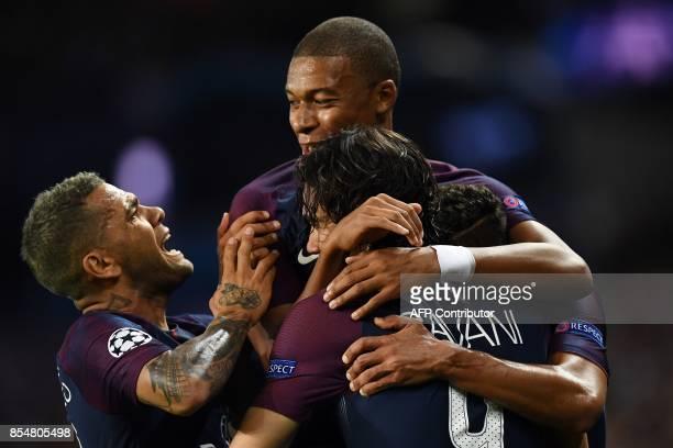 TOPSHOT Paris SaintGermain's Uruguayan forward Edinson Cavani is congratulated by tem mates Paris SaintGermain's French forward Kylian Mbappe and...