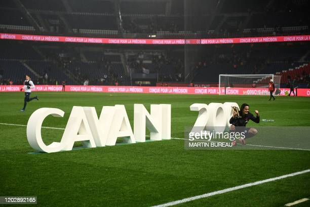TOPSHOT Paris SaintGermain's Uruguayan forward Edinson Cavani poses after receiving a trophy marking his 200th goal for his team after the French L1...