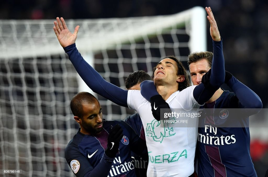 Paris Saint-Germain's Uruguayan forward Edinson Cavani takes off his jersey as he celebrates his goal during the French L1 football match between Paris Saint-Germain and Angers at the Parc des Princes stadium in Paris on November 30, 2016. Cavani took off his jersey to reveal a shirt with Brazil's football team Chapecoense's crest drawn on with the word 'Fuerza' which means 'Force' or 'Strength'. A plane crash that occured in Colombia on November 28, 2016 killed most of Brazilian football club Chapecoense Real and 20 journalists traveling with them to a championship match. Cavani received a yellow card for his gesture. /