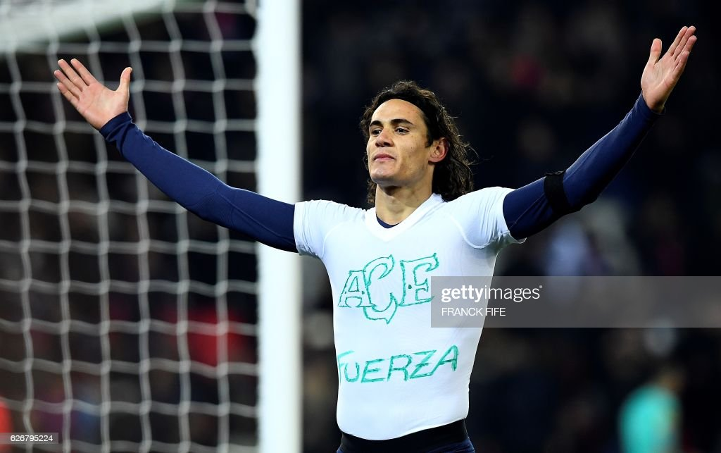 TOPSHOT - Paris Saint-Germain's Uruguayan forward Edinson Cavani takes off his jersey as he celebrates his goal during the French L1 football match between Paris Saint-Germain and Angers at the Parc des Princes stadium in Paris on November 30, 2016. Cavani took off his jersey to reveal a shirt with Brazil's football team Chapecoense's crest drawn on with the word 'Fuerza' which means 'Force' or 'Strength'. A plane crash that occured in Colombia on November 28, 2016 killed most of Brazilian football club Chapecoense Real and 20 journalists traveling with them to a championship match. Cavani received a yellow card for his gesture. /