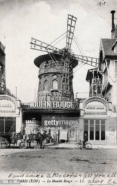 Paris scene 13th arrondisement Le Moulin Rouge famous for its cabaret shows Horse and carriage drawn up outside