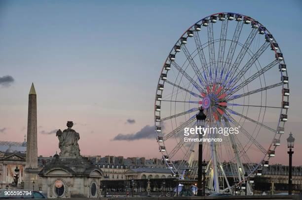 Paris skyline with obelisk and Ferris wheel at sunset.