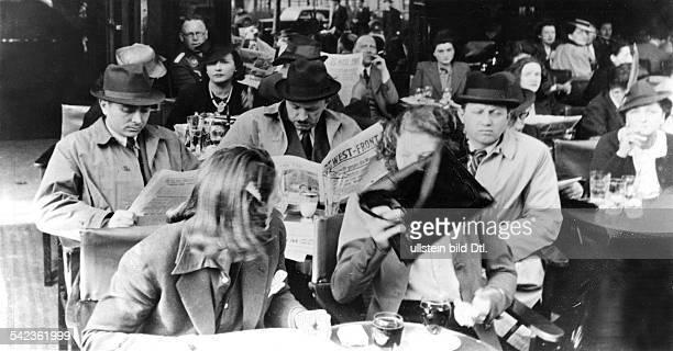 Paris, Strassencafe: Gäste mit deutschen Zeitungen, eine Frau, die nicht fotografiert werden möchte, verdeckt ihr Gesicht mit ihrer Handtasche-...