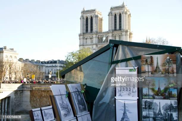 pariser straßenmarkt mit französischen souvenirs entlang der seine und der kathedrale notre dame - graphischer druck stock-fotos und bilder