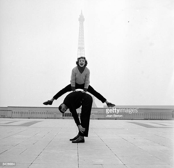 Paris street performers Jean Louis Bert and Grethe Bulow playing leapfrog in front of the Eiffel Tower