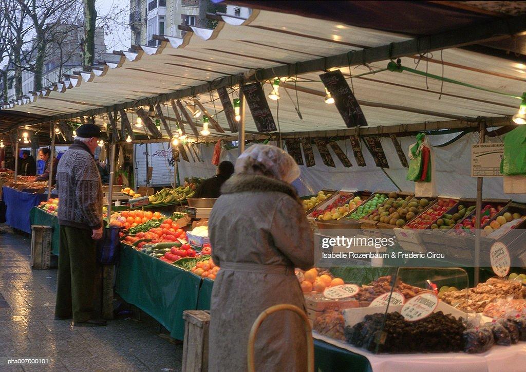 Paris, street produce market, two elderly people, rear view, facing stalls : Stockfoto