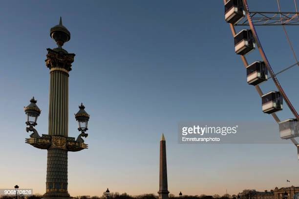 paris sunset with lamp post,obelisk and ferris wheel. - emreturanphoto stock-fotos und bilder
