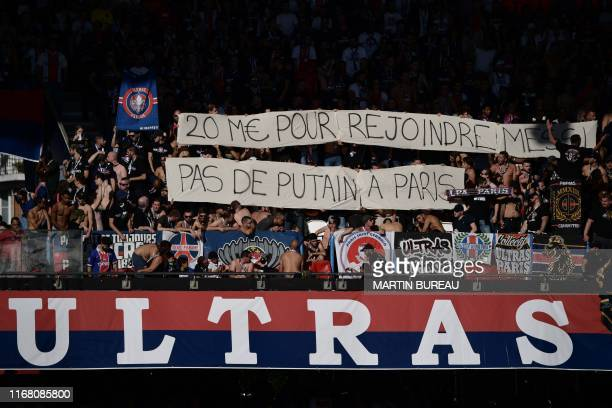 Paris' supporters hold banners reading 20 millions euros to go back to Messi No bitch in Paris during the French L1 football match between Paris...