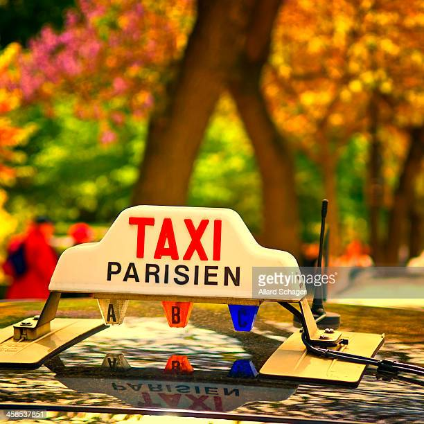 Paris Taxi logo on top of Taxi at Taxi stand near the Eiffel Tower, Paris, France. Captured on sunny spring day with selective focus and shallow...