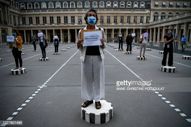 Paris' tour guides hold placards protesting for their working conditions due to the novel coronavirus disease outbreak as they stand on columns of...