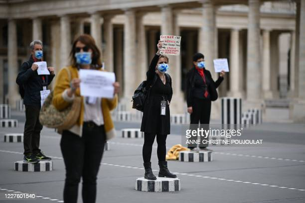 Paris' tour guides hold placards protesting for their working conditions due to the novel coronavirus disease outbreak, as they stand on columns of...
