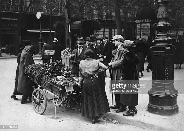 A Paris trader sells bunches of muguet portebonheur good luck lilyofthevalley for fifty centimes on the 1st May the Fete du Muguet circa 1920