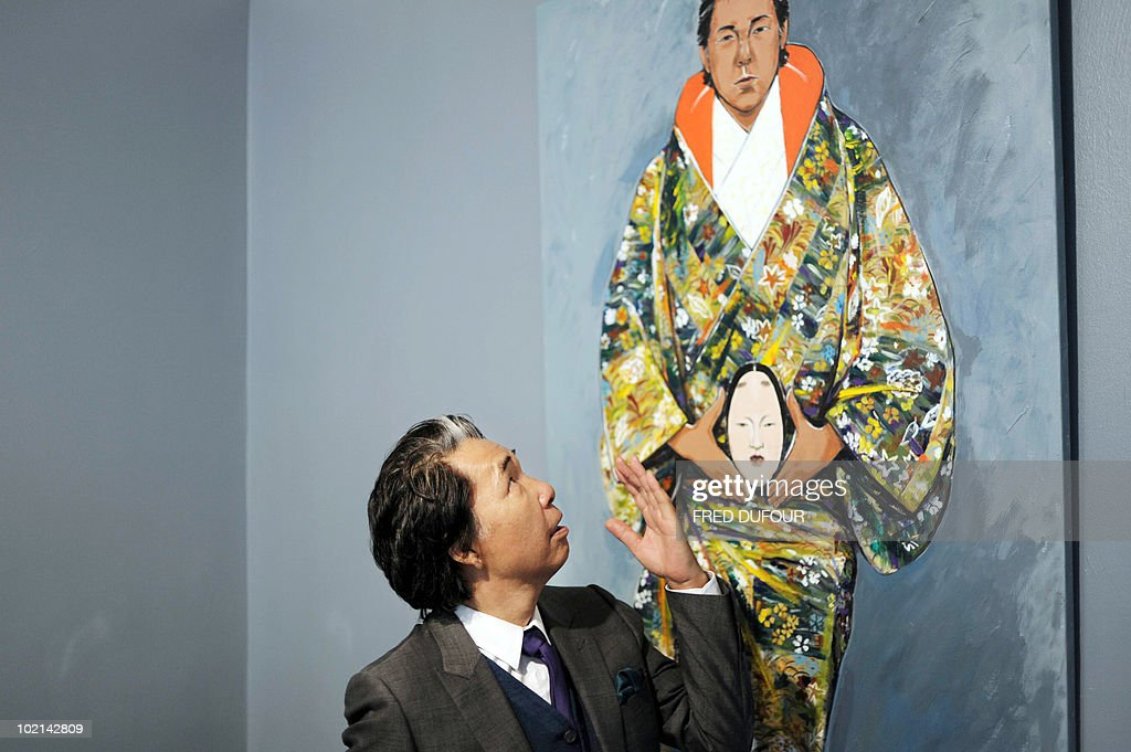 Paris-based Japanese designer Kenzo Takada, aka 'Kenzo', poses in front of one of his self-portrait paintings on June 16, 2010 in Paris prior to the opening of an exhibition at the Studio 55 gallery presenting notably Kenzo's art work. The collective exhibition intitled 'a certain way of life' runs until July 10, 2010.
