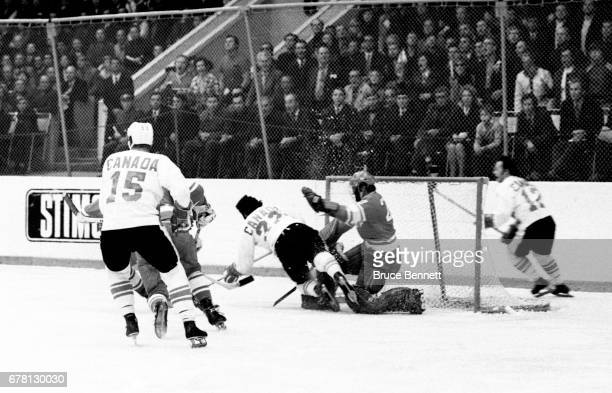 P Parise of Canada crashes into goalie Vladislav Tretiak of the Soviet Union as Red Berenson and Yvan Cournoyer of Canada skate by during a game in...