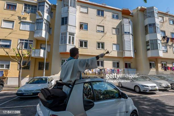 Parish priest of Nova Oeiras e São Julião da Barra Padre Nuno Westwood wears protective mask and gloves as he tolls a bell for residents while...