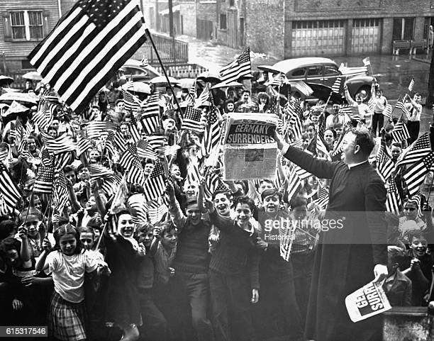 A parish priest waves a newspaper with news of Germany's unconditional surrender to elated pupils of a Roman Catholic parochial school in Chicago