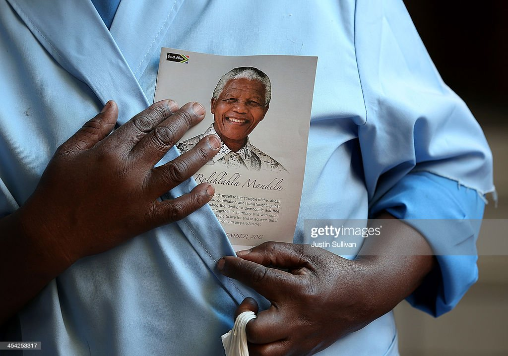 A parishioner holds a pamphlet with the image of Nelson Mandela during church service at Regina Mundi Catholic Church on December 8, 2013 in Soweto, South Africa. Mandela, also known as Madiba, passed away on the evening of December 5th, 2013 at his home in Houghton at the age of 95. Mandela became South Africa's first black president in 1994 after spending 27 years in jail for his activism against apartheid in a racially-divided South Africa.