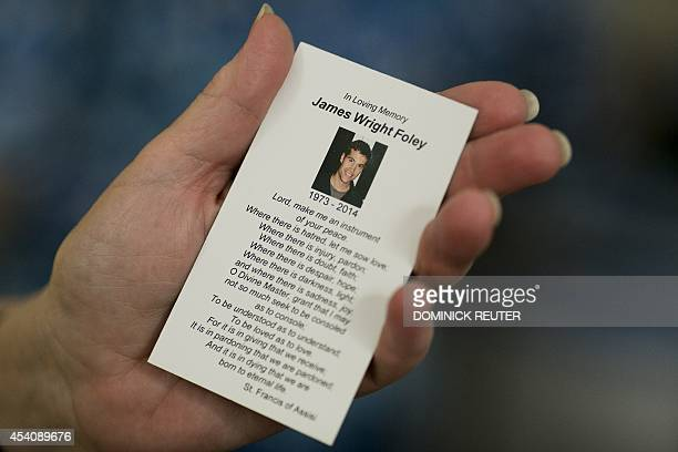 A parishioner holds a prayer card in memory of James Foley after a Catholic mass at Our Lady of the Holy Rosary parish August 24 in Rochester New...