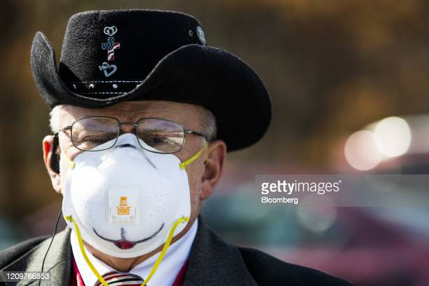 Parishioner wears an N95 mask during a drive-in service on Easter Sunday at the Lighthouse Baptist Church in Hudson, New Hampshire, U.S., on Sunday,...