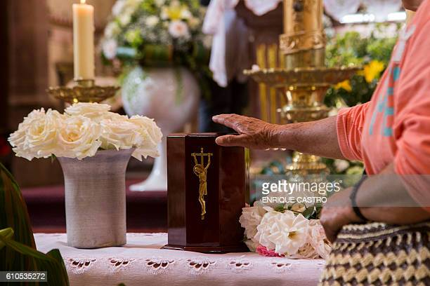Parishioners and friends show their respect to the urn with the ashes of Catholic priest Jose Alfredo Lopez in the Santisima Trinidad church in the...