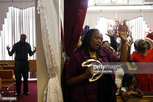 Parishioners and visitors sing during a Sunday service at the Full Gospel Apostolic Church of God/La Mission Chretenee D'Haiti where representatives...