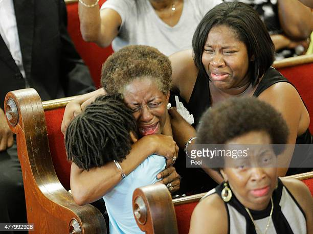Parishioners embrace as they attend the first church service four days after a mass shooting that claimed the lives of nine people at the historic...