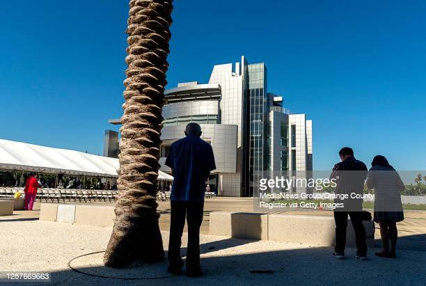 Parishioners gather in the shade of Christ Cathedral during an outdoor mass at Christ Cathedral in Garden Grove on Sunday, July 19, 2020. Services at...