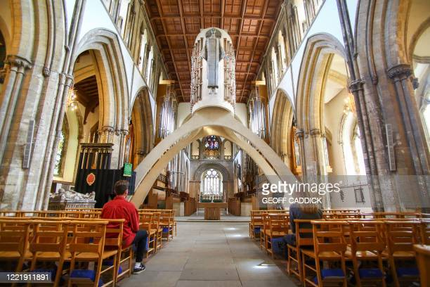 Parishioners observe social distancing measures as they sit inside at Llandaff Cathedral, which has re-opened for private prayer, in Cardiff on June...