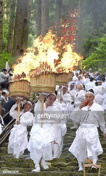 Parishioners of the longestablished Shinto shrine of Kumano Nachi Taisha carry 12 large pine torches during the annual Nachi Fire Festival one of the...