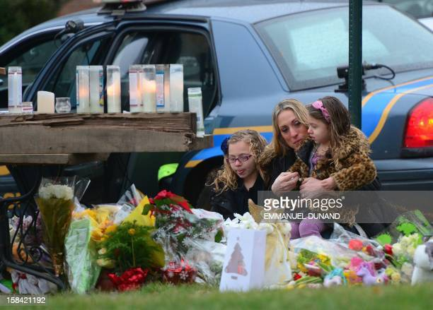 Parishioners pay their respects to the victims of an elementary school shooting while arriving for mass at St Rose of Lima Church in Newtown...