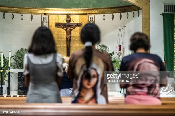 Parishioners pray during mass in St Joseph's Catholic Church near the site of a collapsed building in Surfside, Florida, north of Miami Beach, on...