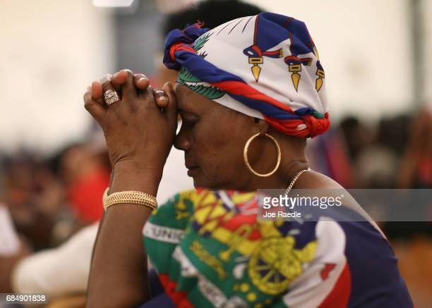 Parishioners pray together during a service at the Notre Dame D'Haiti Catholic Church as they celebrate Haitian Flag day in the Little Haiti...