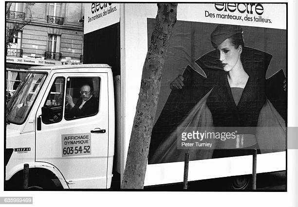 A Parisian billboard company truck is decorated with clothing advertisements
