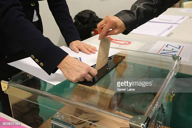 Parisian casts their vote during the first round of voting in the Republican Party's primary elections at a polling station in the 15th...