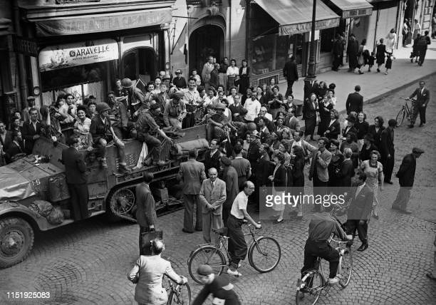 Parisian people welcome soldiers of the French 2nd Armored Division and allied troops on halftrack vehicles, on August 25 in Paris, during the battle...