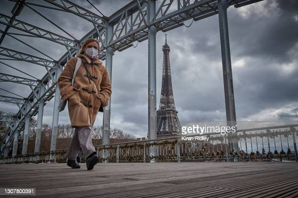 Parisian walks across the river Seine in front of the Eiffel Tower on March 18, 2021 in Paris, France. Today, Prime Minister Jean Castex announced a...