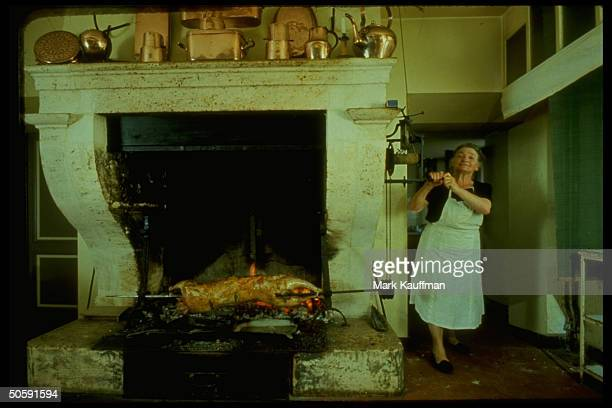 Parisian woman standing next to huge open fireplace w roast on spit in front