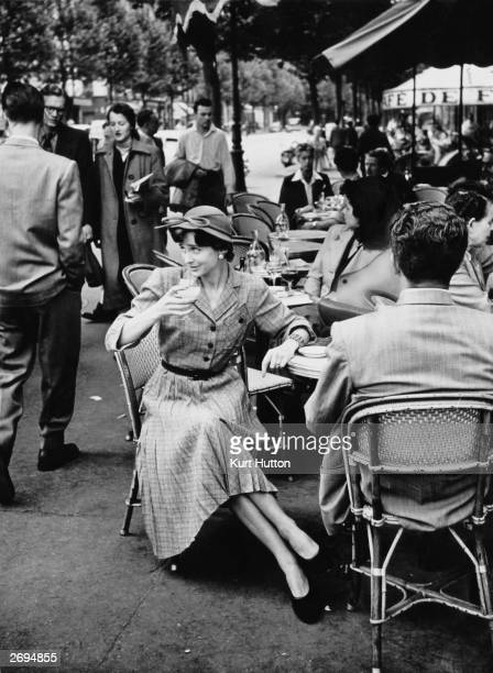 A Parisian woman wearing a British dress of pleated greygreen check drinks an aperitif in a cafe in St Germain des Pres Original Publication Picture...