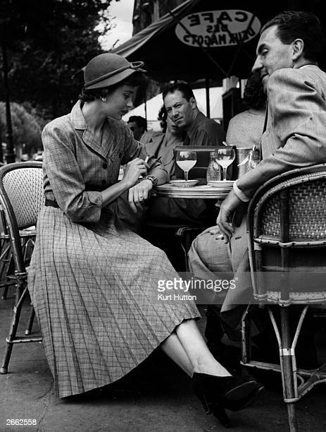 A Parisian woman wearing a massproduced Norman Hartnell design sits at a cafe in St Germaine des Pres Paris These dresses are on sale at Paris...