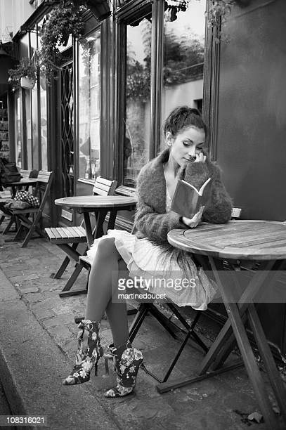 Parisian young lady lost in her taught at sidewalk cafe.