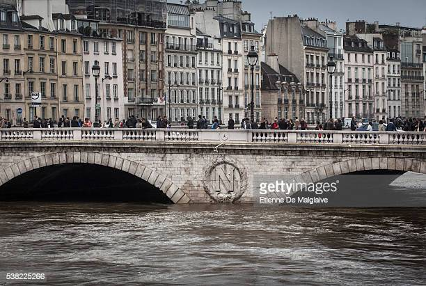 Parisians and tourists cross over the Seine on the Saint Michel bridge as the Seine river's embankments overflow after five days of heavy rain on...